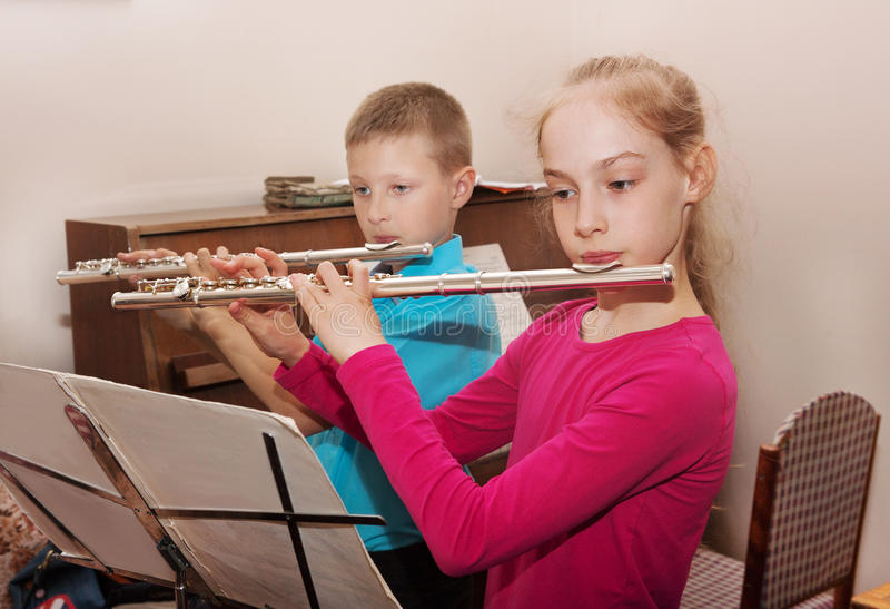 A boy and a girl playing the flute stock photo