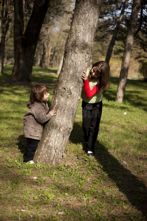 Boy and girl playing in forest stock photos