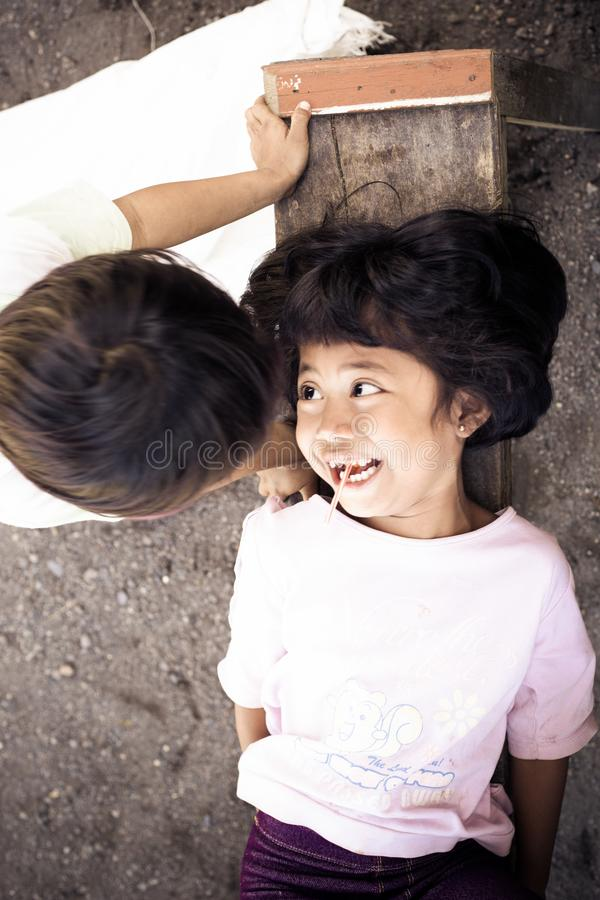Boy and girl playing happily outdoors in a village despite poor living royalty free stock photo