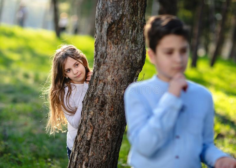 Boy and girl playing hide and seek in the park. Girl watching on boyfriend. royalty free stock images