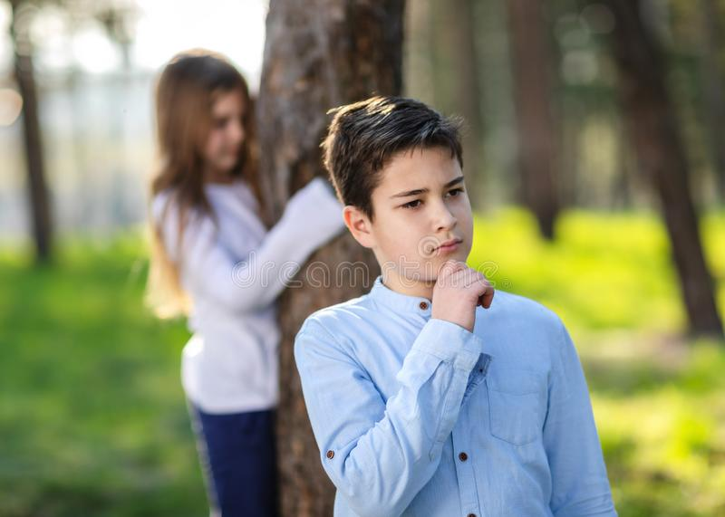 Boy and girl playing hide and seek in the park. Girl watching on boyfriend. stock photo