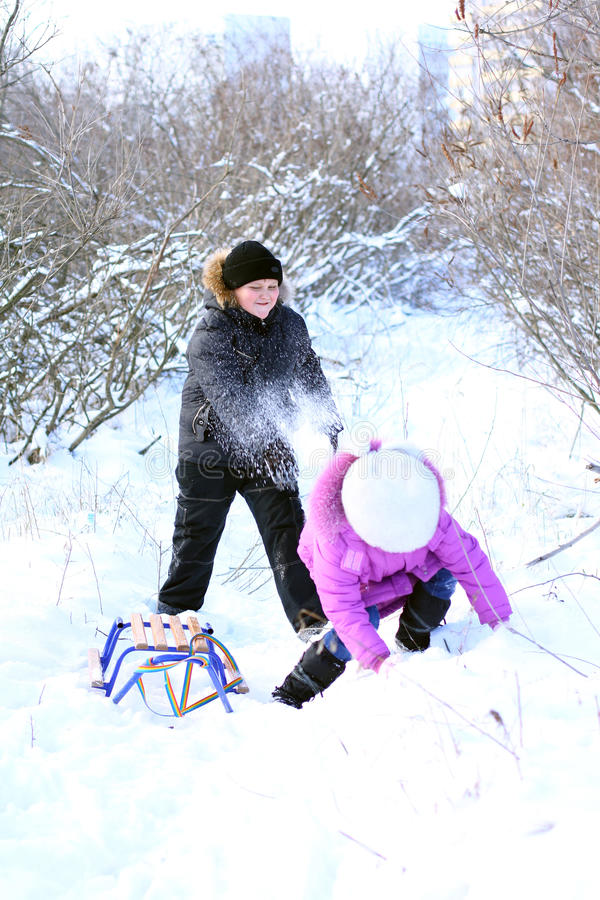 A boy and a girl are playing with snow royalty free stock photo