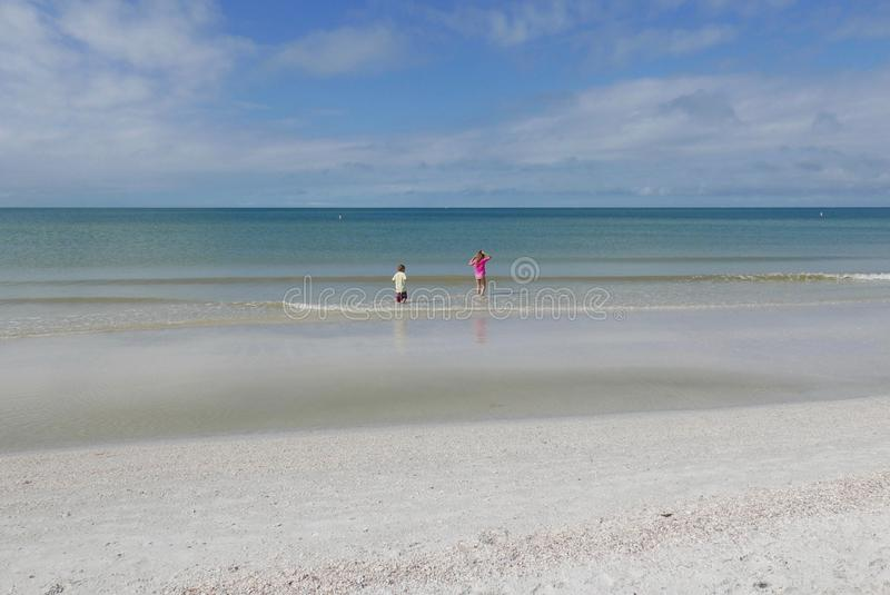 Boy and girl playing in the water at St. Pete Beach, Florida, USA. A young girl and boy are wading and playing in the water at St. Pete Beach, Florida, United royalty free stock image