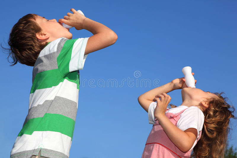 Boy And Girl With Pleasure Drink Yoghurt Royalty Free Stock Photo