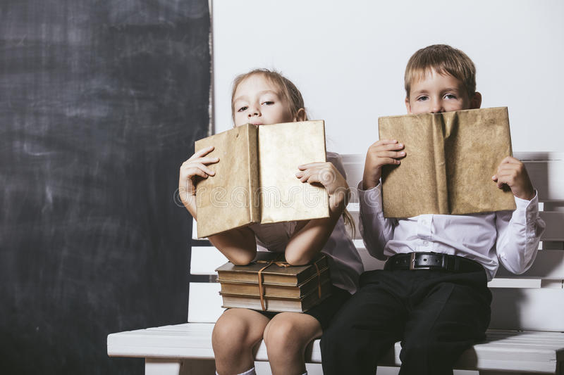 Boy and girl from primary school class on the bench read books o royalty free stock photo