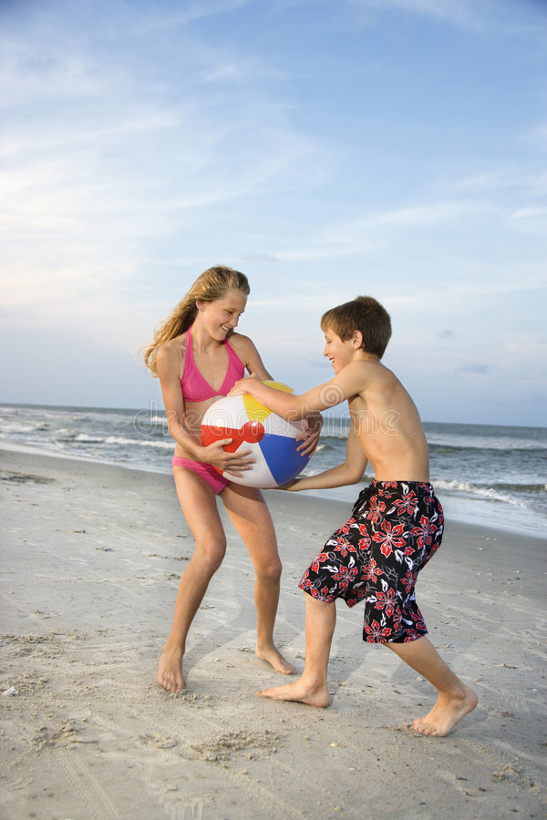 Boy and girl pulling on ball stock photo
