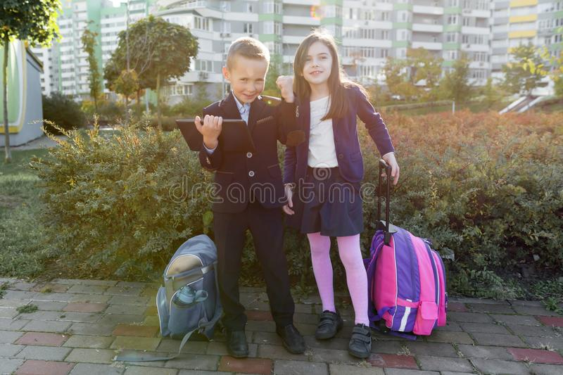 Boy and girl pupils in primary school with digital tablet. Outdoor background, children with school bags, look at the tablet stock image