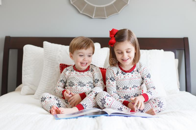 Boy and girl reading on bed with Christmas pajamas royalty free stock photography