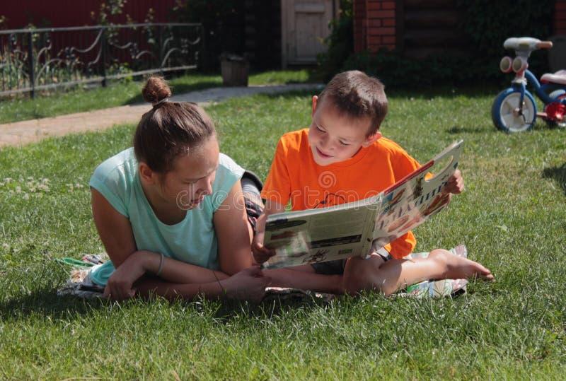 Boy and girl reading book stock photos