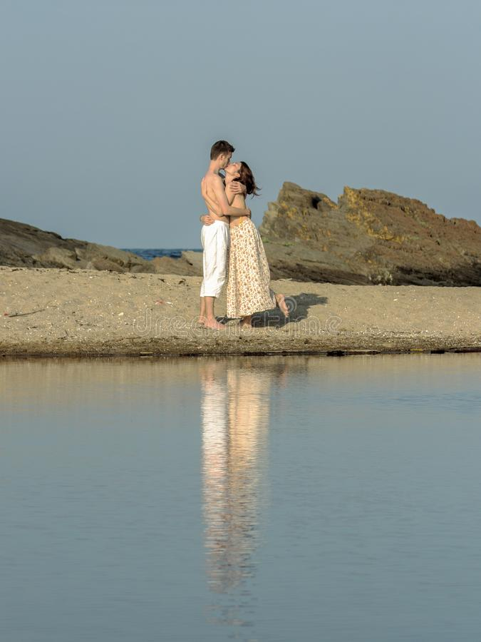 Boy and girl reflected in the lagoon between the mouth of the river and the sea. stock image