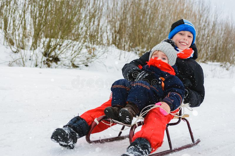 Boy and girl are riding on sleds royalty free stock photography