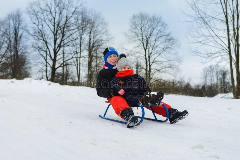 Boy and girl are riding on sleds stock photos