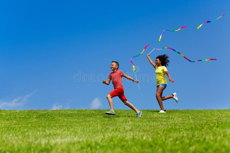 Boy and girl run with long color ribbons over sky stock photo