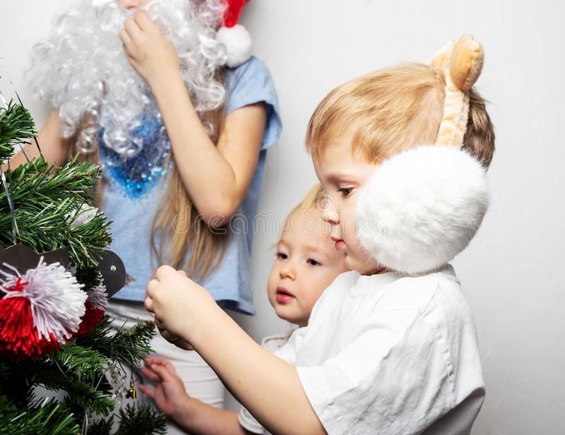 Boy and a girl in a Santa cap decorate a Christmas tree. Family portrait. stock photo