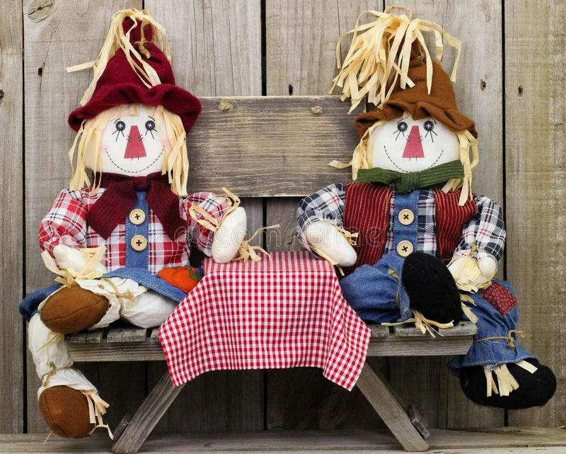Boy and girl scarecrows sitting at picnic table with blank rustic wood sign stock image