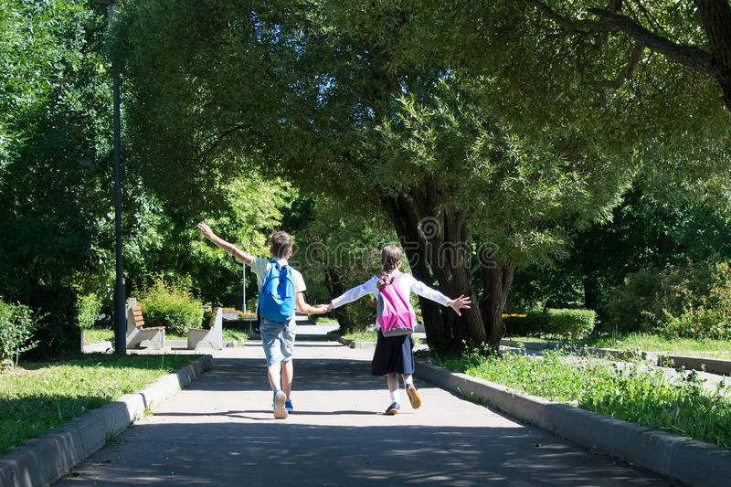 Boy and girl after school with bags full of textbooks returning home through the park holding hands royalty free stock images