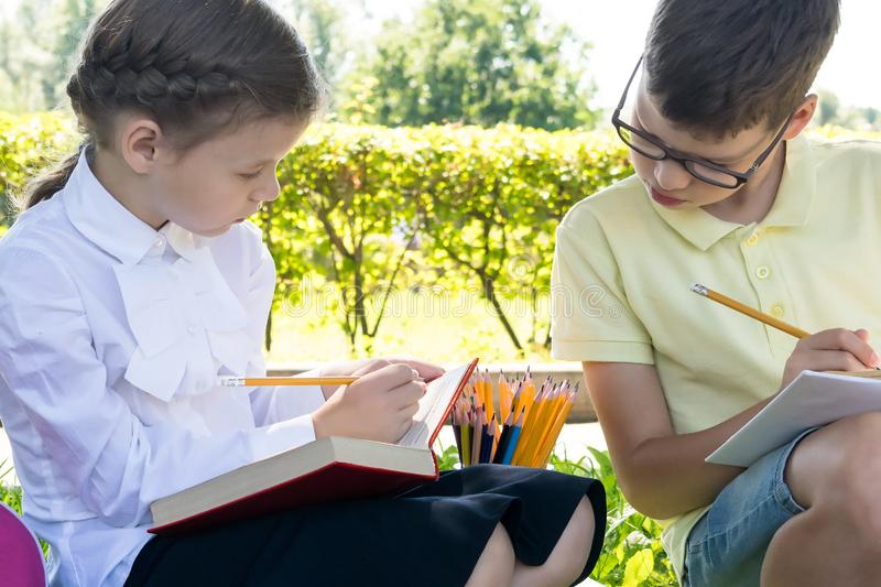 A boy and a girl in school uniform do their homework while sitting in a park on the road on a warm autumn day royalty free stock image