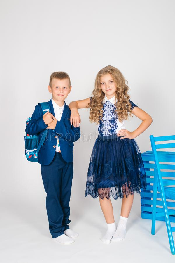 Boy and girl schoolchildren in fashionable school clothes with a school bag. On a white background royalty free stock images