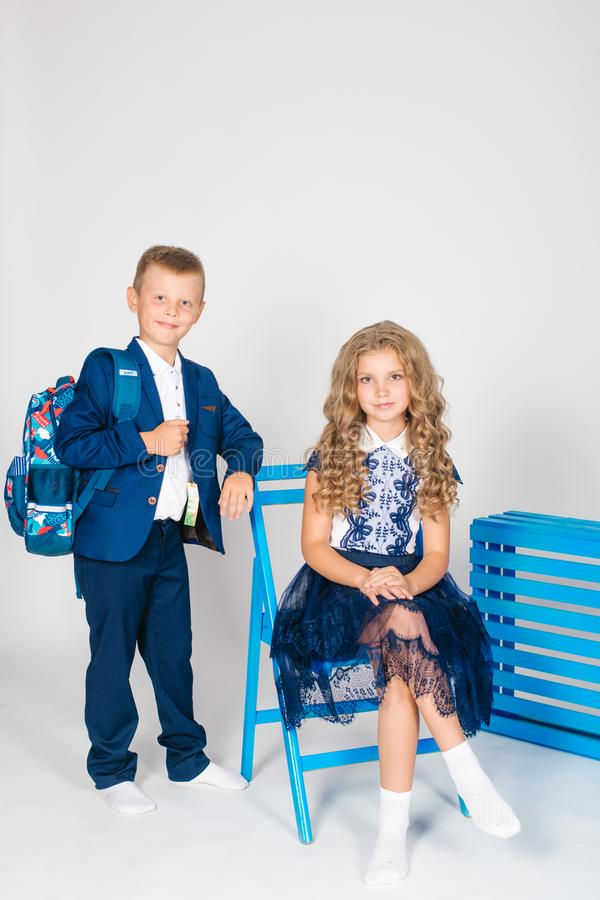 Boy and girl schoolchildren in fashionable school clothes with a school bag. On a white background stock image