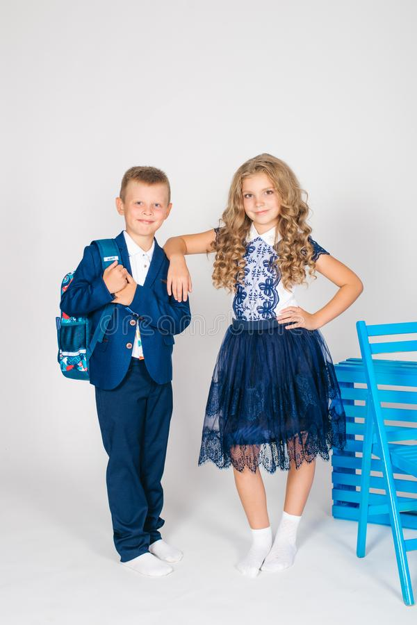 Boy and girl schoolchildren in fashionable school clothes with a school bag. On a white background royalty free stock image