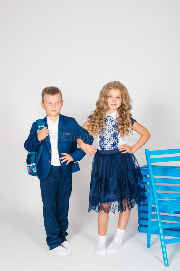 Boy and girl schoolchildren in fashionable school clothes with a school bag. On a white background royalty free stock photos