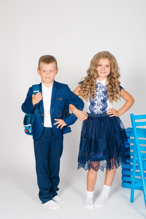 Boy and girl schoolchildren in fashionable school clothes with a school bag. On a white background stock images
