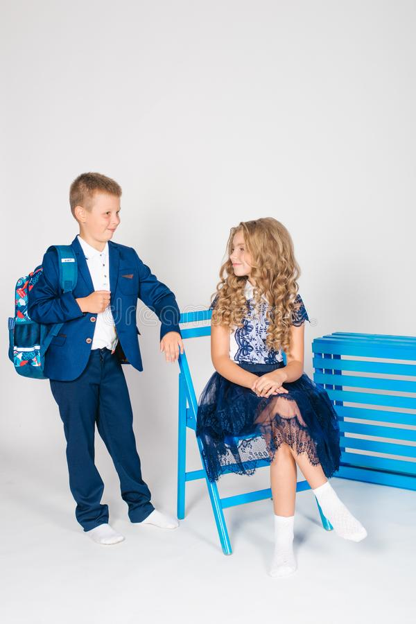 Boy and girl schoolchildren in fashionable school clothes with a school bag. On a white background stock photos