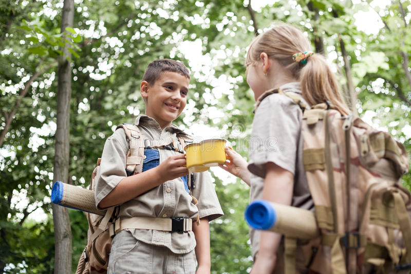 Boy and a girl scouts on a camping trip in the woods. Excited children on a camping trip in green forest royalty free stock photography