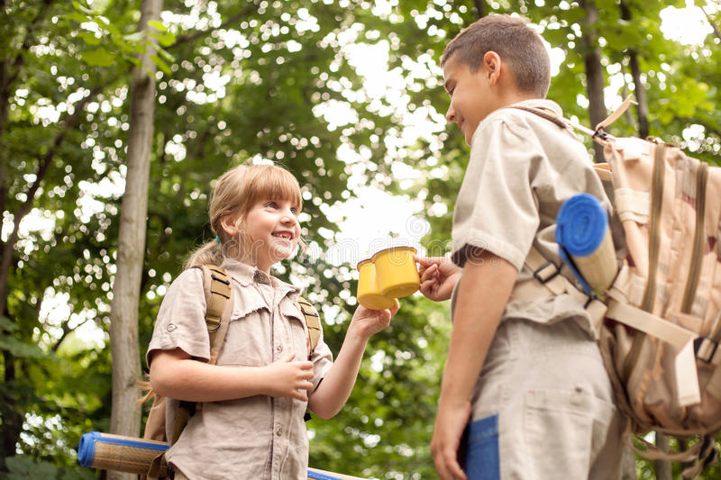 Boy and a girl scouts on a camping trip in the woods. Excited children on a camping trip in green forest stock photos
