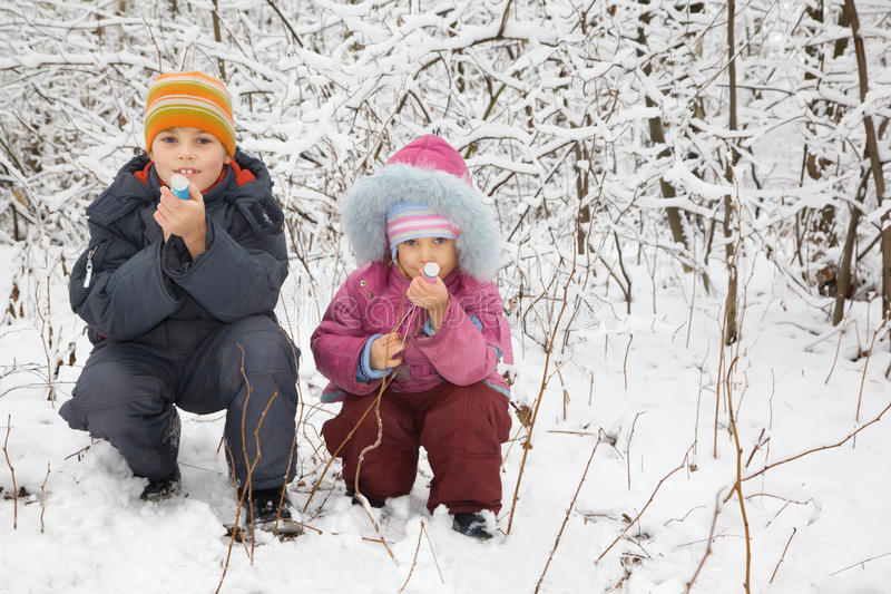 Boy and girl sit down with petard in winter wood