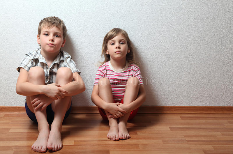 Boy and girl sit leaning on wall