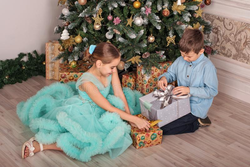 Brother and sister sit near a new year tree and unpack their gift boxes stock image