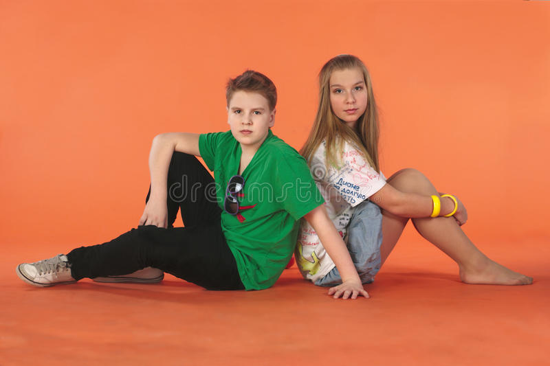 Download Boy And Girl Sitting Back-to-back Stock Photography - Image: 19335942