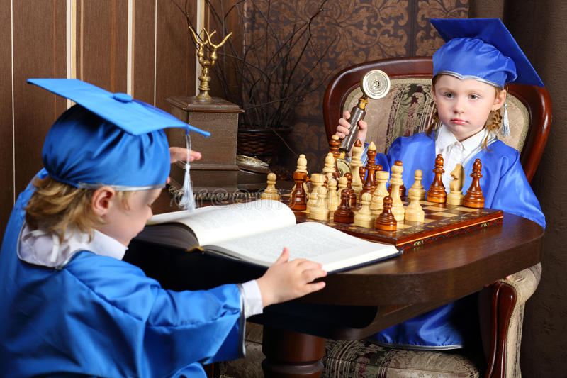 boy and girl sitting at the chess table royalty free stock photo