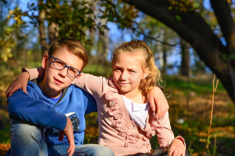 A boy with a girl are sitting on dry leaves in the woods on a summer evening, brother and sister together in nature.  royalty free stock photography