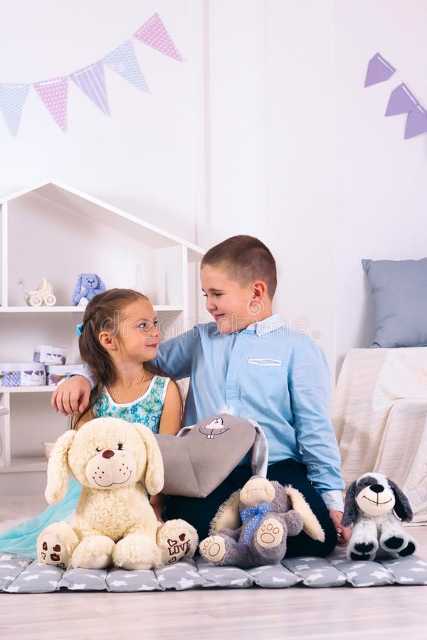 boy and girl sitting on the floor in the children`s room among the toys, the boy hugs the girl and they look at each royalty free stock photography