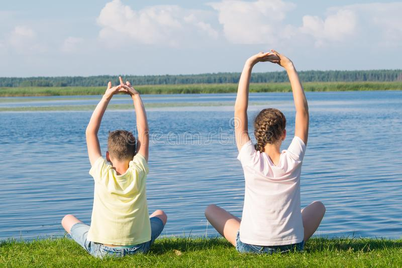 A boy and a girl are sitting on the green grass and doing yoga, holding their hands above their heads, rear view, against the. Background of a beautiful sky and stock photo