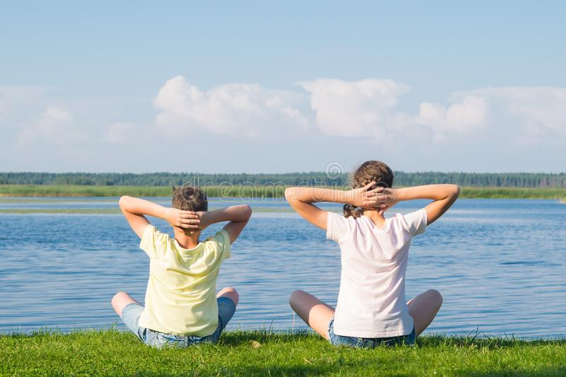 A boy and a girl are sitting on the green grass and doing yoga, holding their hands behind their heads, back view, against the. Backdrop of a beautiful royalty free stock photo