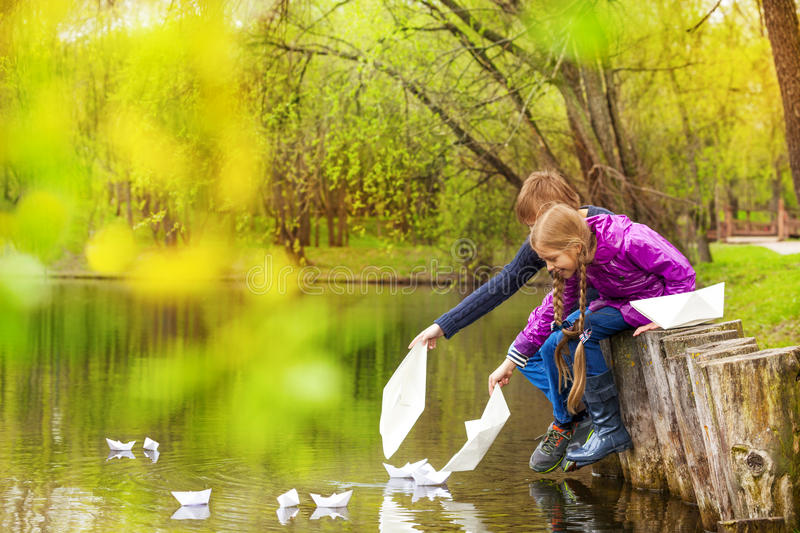 Boy and girl sitting near pond putting paper boats royalty free stock photo