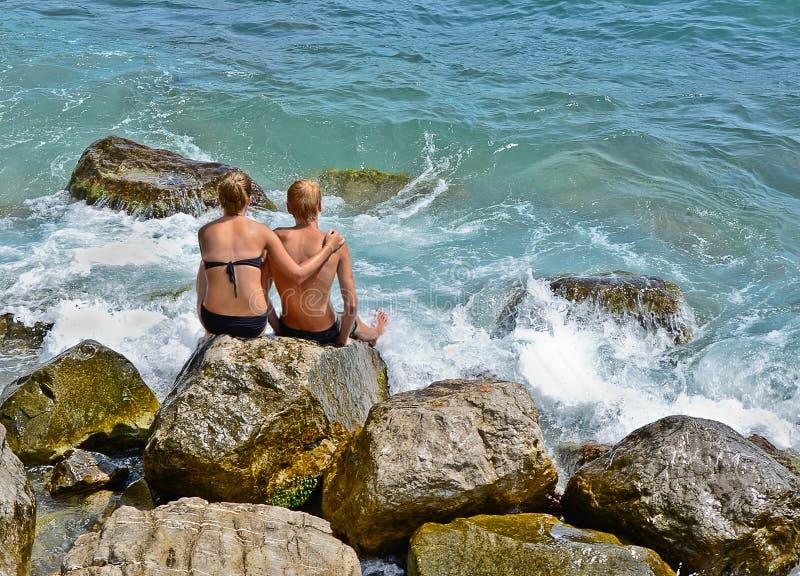 Boy and girl sitting near the sea stock photo