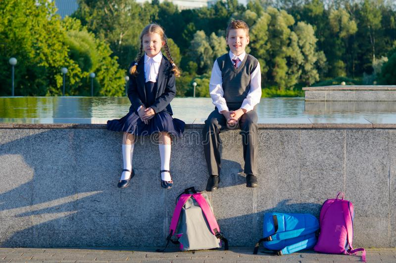 Boy and girl are sitting together in the park after school royalty free stock photo
