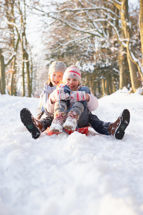 Boy And Girl Sledging Through Snowy Woodland stock image