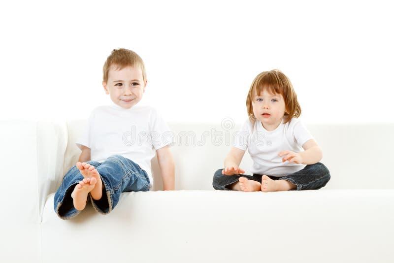 Boy and girl on sofa stock photos