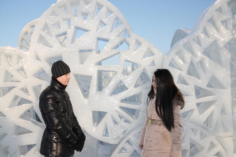 Boy and girl stand near ice wall with triangular holes stock photo