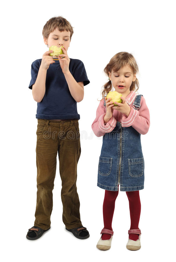 Boy and girl standing and eating big apples. Little boy and girl standing and eating big apples isolated on white stock photo