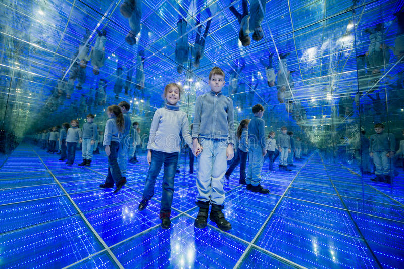 Boy and girl standing in a mirrored room. With blue lights holding hands royalty free stock photo