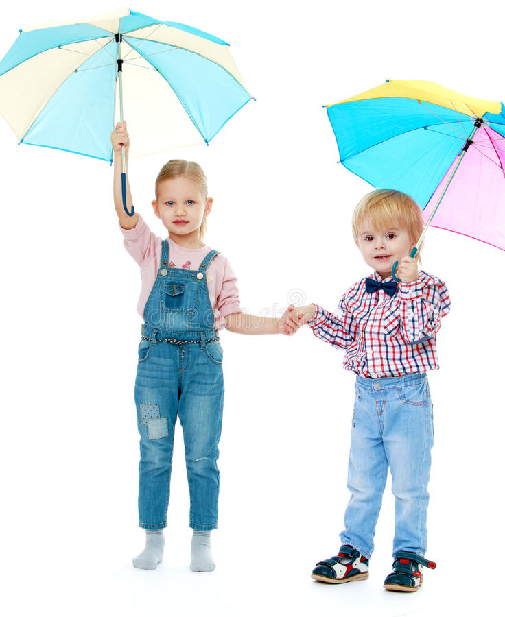 Boy with a girl standing. Under a multi-colored umbrellas.Childhood education development in the Montessori school concept. Isolated on white background stock photos