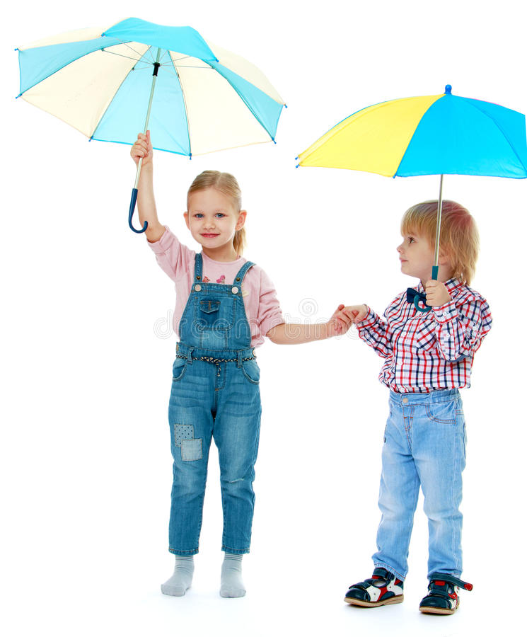 Boy with a girl standing. Under a multi-colored umbrellas.Childhood education development in the Montessori school concept. Isolated on white background stock images