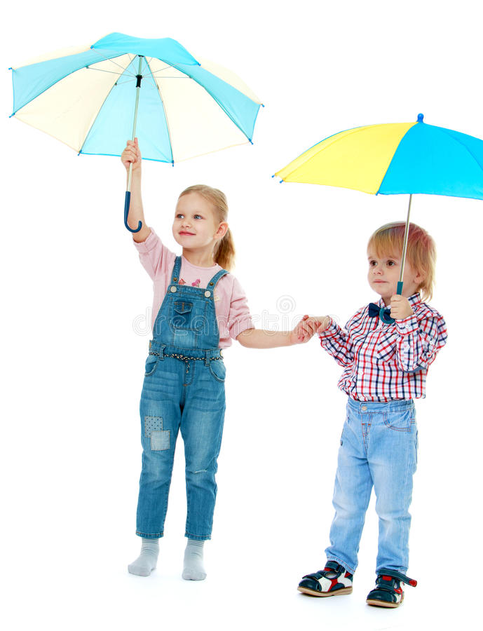 Boy with a girl standing. Under a multi-colored umbrellas.Childhood education development in the Montessori school concept. Isolated on white background royalty free stock images