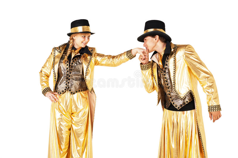 Boy and girl on stilts. Boy and girl, dressed in golden, staying on stilts. Boy kissing girls hand stock photography